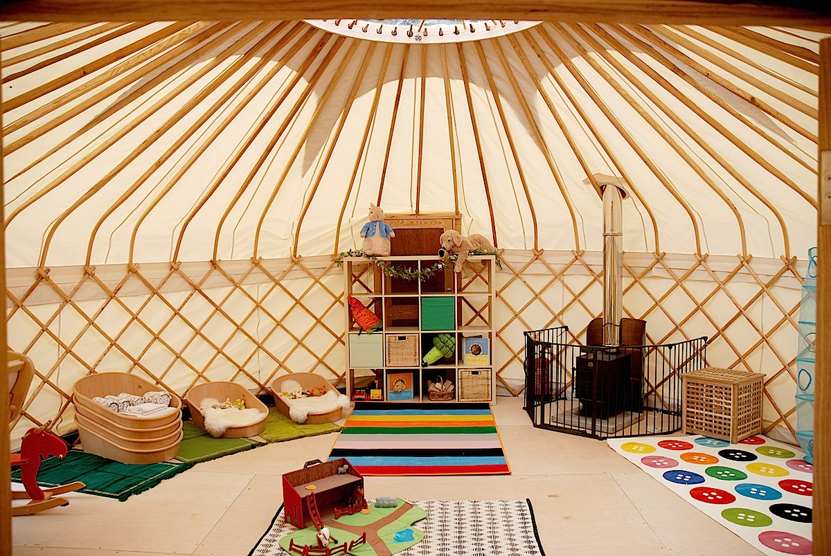 Yurt styled for used as a children's playroom with a fire-guard around the wood burning stove