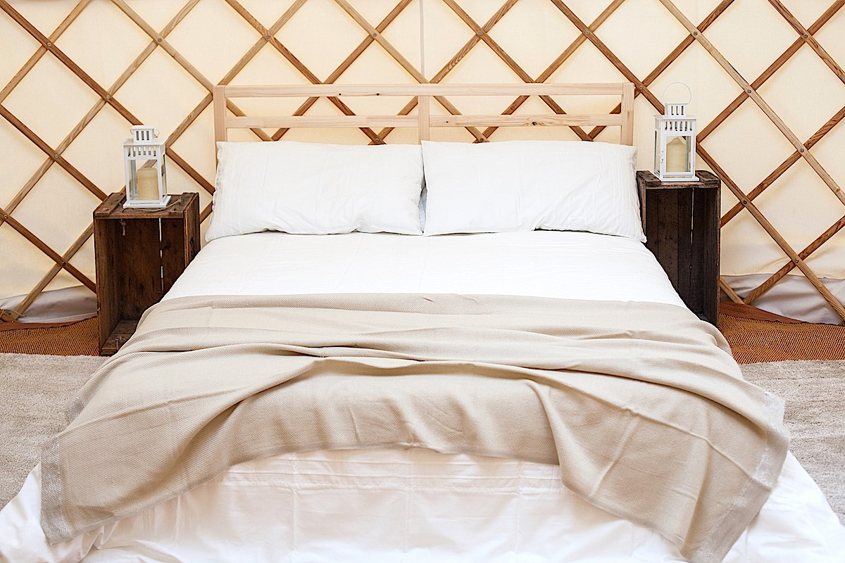 Style your yurt with a double bed and white linen