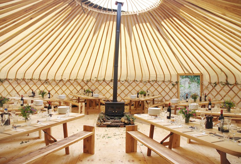 30ft Yurt styled for dining with a wood-burning stove in the centre.