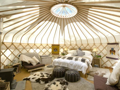 sapperton-16ft-yurt-view-of-interior-space-with-bed-and-wood-burner